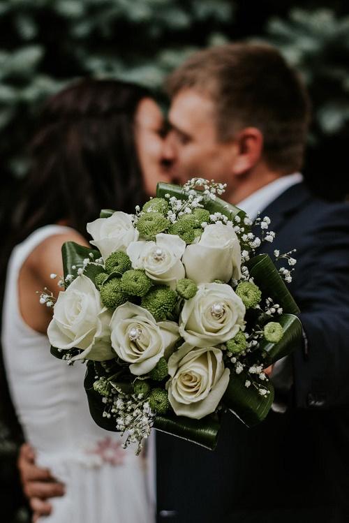 Букет белых роз на фоне целующейся пары
