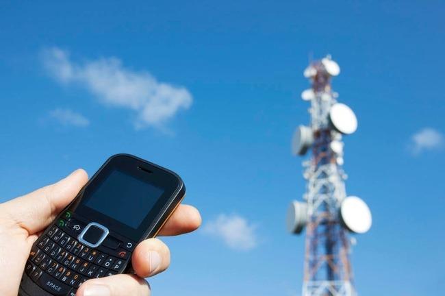 Телефон на фоне вышки сотовой связи