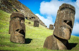 Моаи стоят на зеленом холме на фоне голубого неба