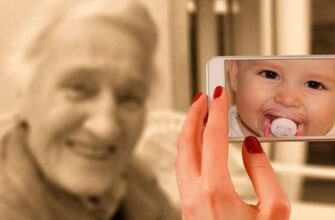 Смартфон с лицом ребенка на экране на фоне улыбающейся бабушки