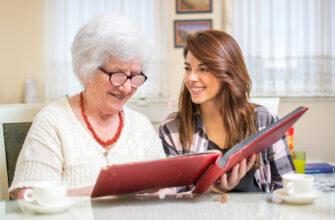 Бабушка и девушка просматривают фотоальбом