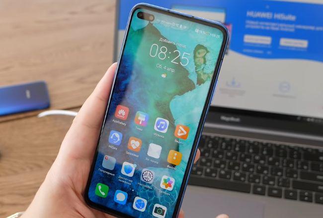 Телефон Huawei в руке на фоне ноутбука